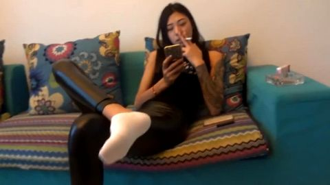 Tattooed Asian teenage girl in tight pants plays with her feet while chilling on the sofa