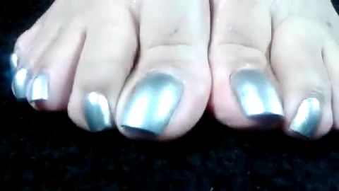 Mature woman revealing her long nails with sexy grey nail polish on them