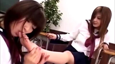 Attractive Asian schoolgirls suck each other's teenage toes in the classroom