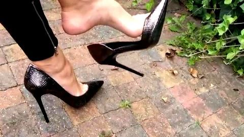 Fantastic sophisticated girl dangling her quality stiletto shoes in public