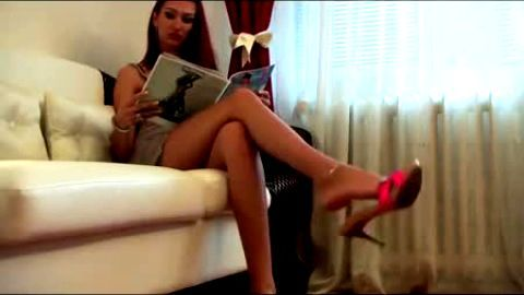 Bitch redhead dangling her pink mules while reading magazine on the sofa
