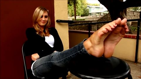 Glorious blonde wearing tight jeans while talking about her pretty feet outdoors