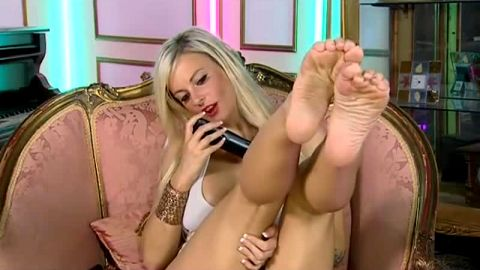 Big breasted blonde talks on the phone while touching her beautiful feet