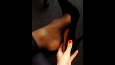 Kinky babe plays with her super sexy black shoes at the office
