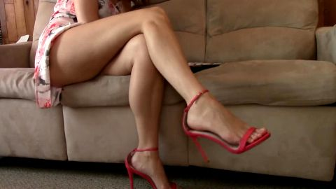 Wonderful woman in sexy summer dress sitting on the sofa in homemade shoeplay action