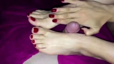 Incredibly sexy feet with beautiful red toe nails playing with a hard dick in bed