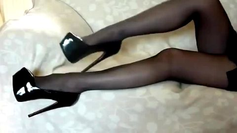Sophisticated girl in stockings dangling her super sexy high heel shoes in bed