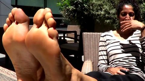 Lovely ebony girl sunbathing her exotic black feet and toes on vacation