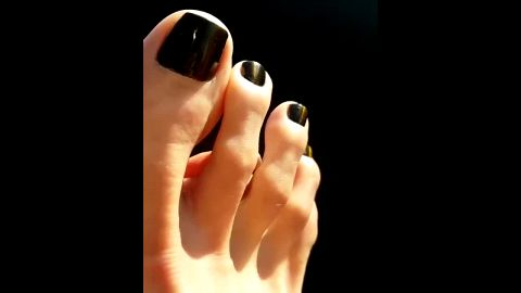 close up long toes black polish