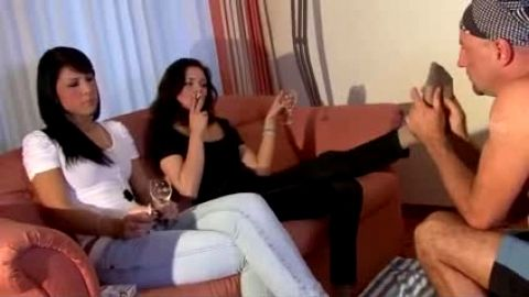 Sexy girlfriends receiving an amazing foot massage while drinking wine on the sofa