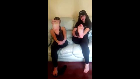 Teenage girlfriends in black outfits showing off their delicious feet together
