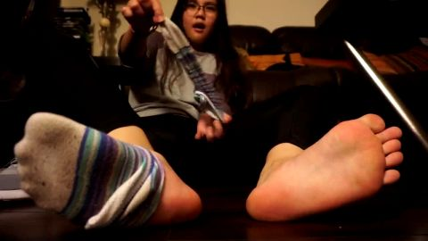 Asian babe shows her exotic feet while playing with stinky socks on the floor