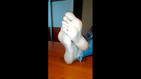 Amateur goddess in tight jeans reveals her attractive soles while resting her legs on the table