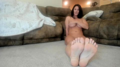 Big boobed MILF shows her perfect feet while spreading her legs on the floor