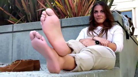 Beautiful brunette chilling during lunch break revealing her phenomenal naked feet