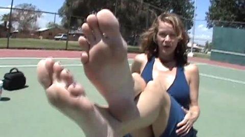 Wonderful big tit MILF in tight dress flaunts her mature feet on the tennis court