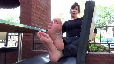 Middle aged lady getting her beautiful feet with red toe nails tickled