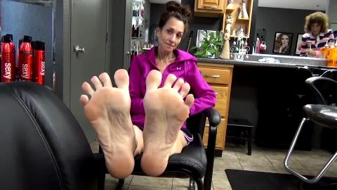 Skinny woman showing off her gorgeous mature feet with purple toe nails at beauty salon