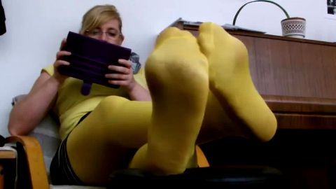 Nerdy mature woman in sexy yellow nylon stockings reading ebook on the tablet
