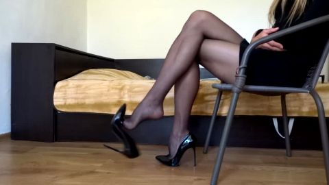 Sophisticated blonde in sexy black uniform sitting in the chair dangling her stiletto shoes