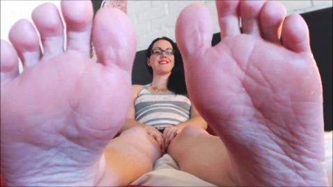 Amateur chick with glasses gets rid of her colorful socks and exposes her soles close up