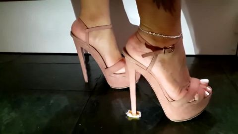 Amateur woman in sexy shoes crushing a candy with her monster high heels