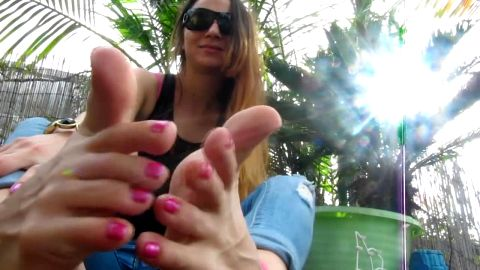 Hottie with sunglasses knows how to play with her sensitive toes and feet in the garden