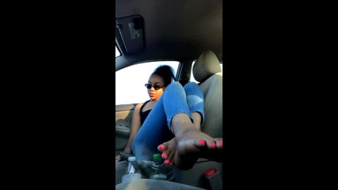 Bored ebony bombshell shows her caramel feet with long orange toe nails in the car