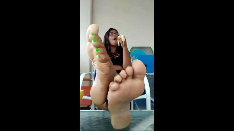 Amateur brunette with glasses sitting in the chair exposing her sexy dark feet