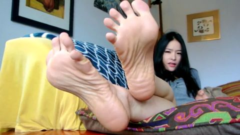 Asian babe loves teasing with her sensitive soles and pink toe nails