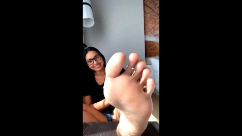 Stunning chick with sexy eyeglasses showcasing her attractive toes and soles