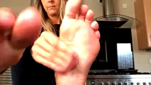 Blonde MILF puts oil on her mature feet and massages them in the kitchen