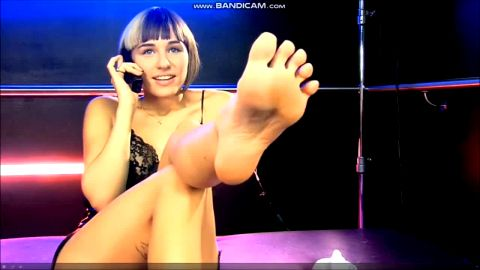 Attractive girl flaunts her exotic feet while talking on the phone