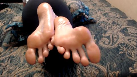 Woman in yoga pants teases with her oily soles and feet