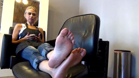 Blonde in sexy jeans gets her sensitive feet tickled in the office chair