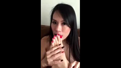 Nude MILF slowly licks her yummy Asian toes on the couch