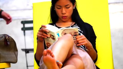 Beautiful Asian girl reveals incredible feet as she reads book in public