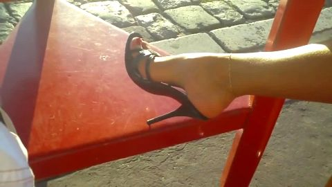 Hottie sunbathing her exotic legs and feet in high heels outdoors