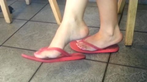 Amateur woman with lovely pink toe nails dangling flip flops in public