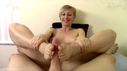 Short haired MILF takes massive facial after giving a POV footjob