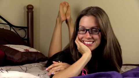 Brunette with cute eyeglasses exposing her wonderful feet while chilling in bed
