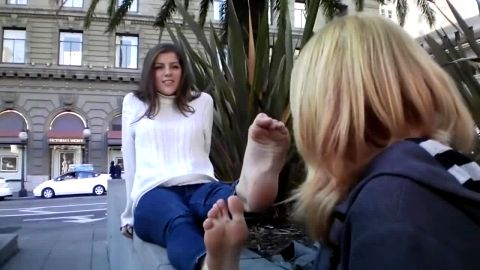 Submissive chick sniffs and worships sexy brunette's dirty feet in public