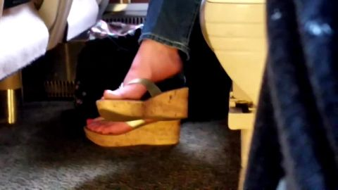 College chick in jeans tries out shoe dangling in the local train