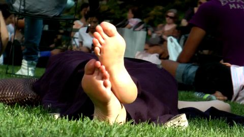 Woman sunbathing her magical feet as she resting on the grass in public