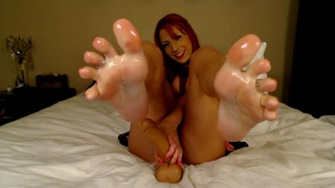 Exotic redhead mistress jerks a plastic meatpole with her hot feet