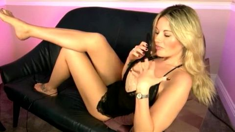 Goddess sitting in provocative black lingerie on the sofa showcasing her hot body and feet